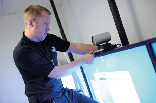 A Man Fitting a Video Conferencing Camera to Duel TV Screens